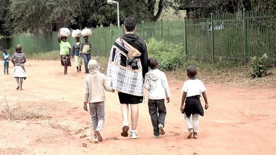 Student walking down the road holding the hands of two children